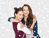 happy pretty teenage girls hugging over snow