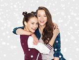 happy pretty teenage girls hugging over snow