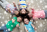 happy kids lying on floor and showing thumbs up