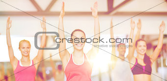 group of smiling people exercising in the gym
