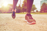 close up of woman feet running on track from back