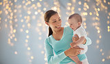 happy young mother with little baby over lights