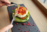 woman eating goat cheese salad at restaurant