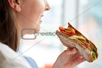 close up of happy woman eating panini sandwich