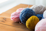 knitting needles and balls of yarn on wood
