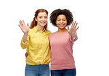 happy smiling women waving hands over white