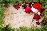 Christmas hat with bauble and fir branches on wood background.