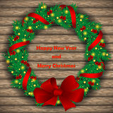 Christmas wreath with baubles and treeon background of boards.
