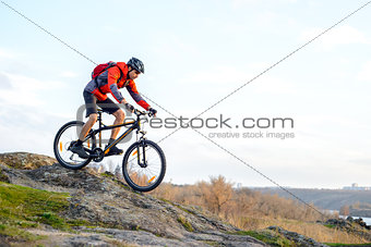 Cyclist in Red Jacket Riding the Bike Down Rocky Hill. Extreme Sport.
