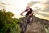 Professional Cyclist Riding the Bike Down Rocky Hill at Sunset. Extreme Sport.