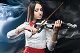 Dreamy woman playing the violin on a black background