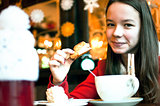 Girl with a cup of tea in a cafe eating Christmas cookies and sm