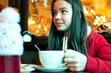 Girl with a cup of tea in a cafe eating Christmas cookies and lo