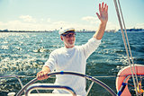senior man at helm on boat or yacht sailing in sea