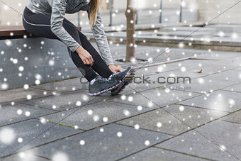 close up of sporty woman tying shoes outdoors
