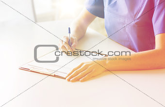 close up of doctor or nurse writing to clipboard