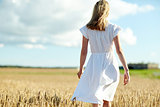 young woman in white dress walking along on field