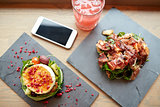 goat cheese and ham salads with smartphone at cafe