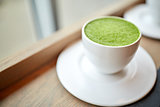 white cup of matcha green tea latte on table