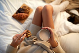 close up of woman with cocoa cup and cookie in bed