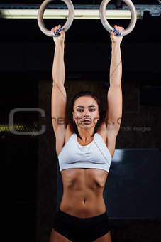 Portrait of young fit muscular girl in white top using gymnastic rings.