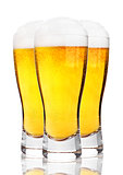 Glasses of cold beer with foam and froth on white
