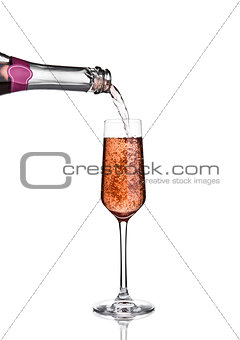 Pouring pink rose champagne from bottle to glass