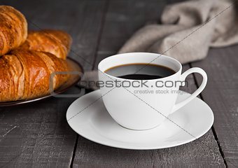 Cup of black coffee and croissant for breakfast