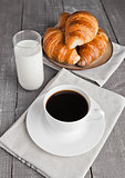 Cup of black coffee and croissant and milk
