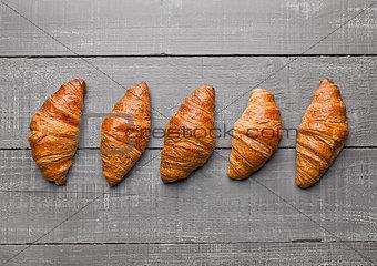 Fresh crispy croissant for breakfast on wood