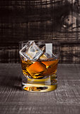 Glasss of whiskey with ice cubes on wood