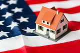 close up of house model on american flag