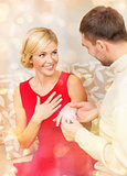 romantic man proposing to a woman in red dress