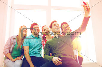 five smiling students taking picture with camera