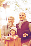 happy family with smartphone and monopod in park