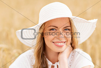 close up of happy woman in sun hat on cereal field