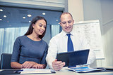 smiling businesspeople with tablet pc in office