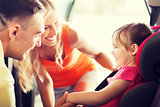 parents talking to little girl in baby car seat