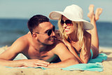 happy couple in swimwear lying on summer beach