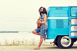 hippie man playing guitar over minivan on beach