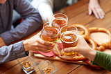 close up of hands clinking beer at bar or pub