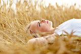 young woman lying on cereal field and dreaming