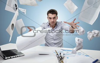 angry businessman throwing papers in office