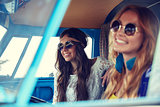 smiling young hippie women driving minivan car