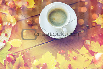 close up of coffee cup on table with autumn leaves