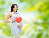 happy pregnant woman with red heart touching belly