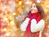 happy woman in scarf and mittens over lights