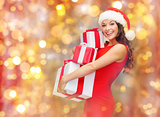 smiling woman in santa hat holding gift boxes