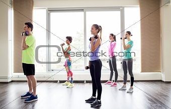 group of smiling people exercising with dumbbells