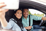 happy couple in car taking selfie with smartphone